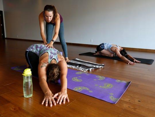 Alex Maurer, owner of Sangha Studio, helps Jen Kilgore,