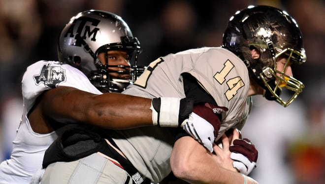 Vanderbilt quarterback Kyle Shurmur (14) is sacked by Texas A&M defensive lineman Alonzo Williams (83)  on  Nov. 21, 2015.