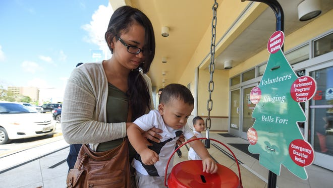 Two-year-old Jaxon Santos is carried by his mother, Anna Santos, while attempting to make a donation to The Salvation Army's Red Kettle at Agana Shopping Center in Hagåtña on Dec. 12, 2017.