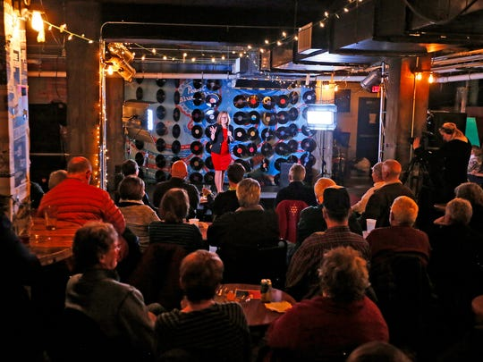 Reporter Mackenzie Ryan takes the stage at the Des Moines Storytellers Project Wednesday, Dec. 2, 2015 at the Des Moines Social Club.