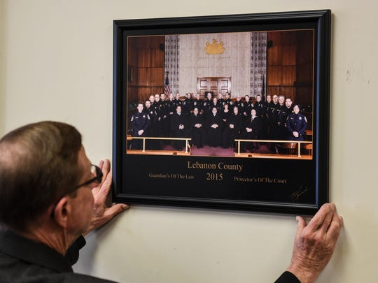 Sheriff Bruce Klingler, hangs the photo after local photographer Robert Howard made of all five Lebanon County judges and all 21 sheriff deputies on Friday, March 4, 2016. This is the first time a picture like this has been taken. The photo was taken on Oct. 19, 2015 and Howard donated his services and the print which hangs in the judge's chambers.