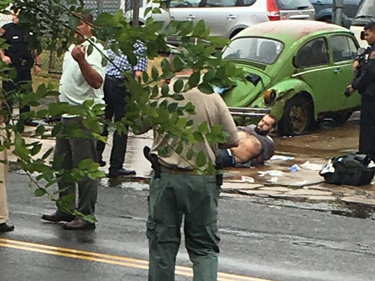 Ahmad Khan Rahami is taken into custody after a shootout with police Monday, Sept. 19, 2016, in Linden, N.J. Rahami was wanted for questioning in the bombings that rocked the Chelsea neighborhood of New York and the New Jersey shore town of Seaside Park.