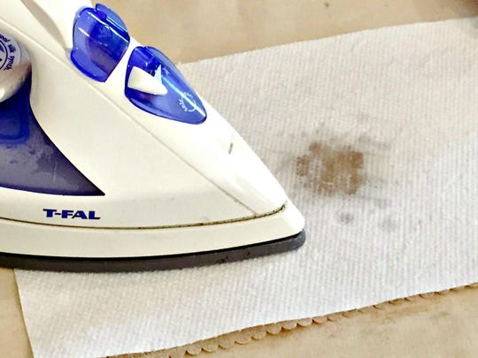 Place a paper towel over the fabric where the wax has dried. With a dry iron set on the lowest setting, iron over the paper towel, allowing it to absorb the melted wax.