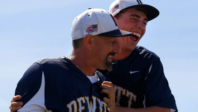 DeWitt's Donovan Tarn, right, celebrates with coach Alan Shankel after soaking him with ice water following their MHSAA Division 2 Regional championship Saturday, June 6, 2015, in Eaton Rapids, Mich.