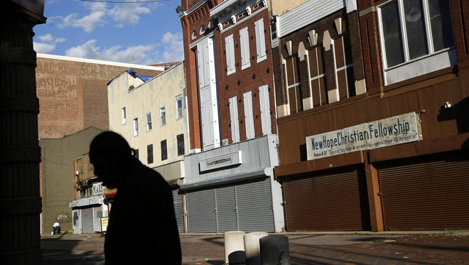 A man walks past vacant storefronts at the Old Town Mall in Baltimore.