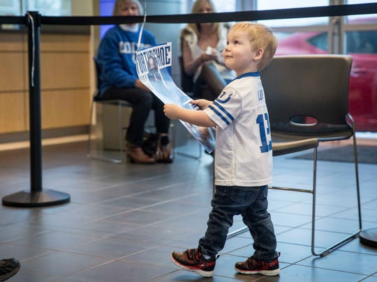 A small Colts fan carries away a signed poster after meeting Robert Mathis Tuesday afternoon at an appearance at Toyota of Muncie. Mathis played for the Colts for 14 years before retiring at the end of this season.