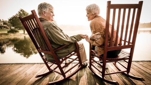 Older couple sitting on a wooden dock.
