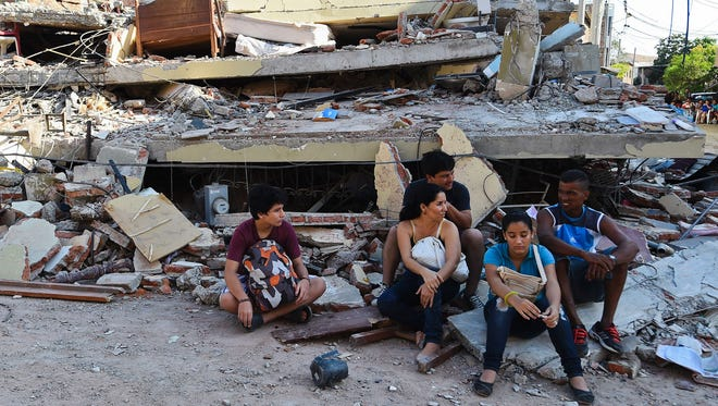People rest in front of a destroyed house in Manta, Ecuador, on April 17, 2016.
