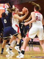 Marist College's Rebekah Hand sneaks a pass through Navy defenders to Willow Duffell at McCann Arena in November.
