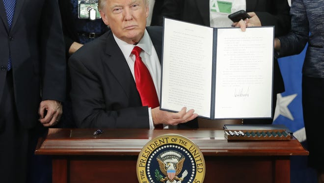 President Donald Trump holds up an executive order for border security and immigration enforcement improvements after signing the order during a Jan. 25 visit to the Homeland Security Department headquarters in Washington.