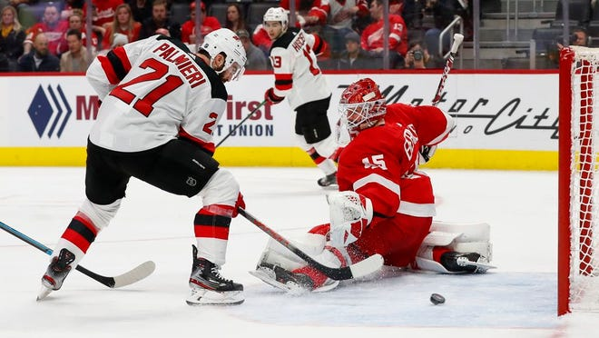 New Jersey Devils right wing Kyle Palmieri (21) scores a goal on Detroit Red Wings goaltender Jonathan Bernier (45) in the second period of an NHL hockey game Tuesday, Feb. 25, 2020, in Detroit.