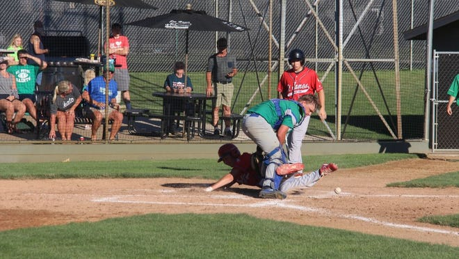 Connor Jones dives in ahead of a throw back home following a passed ball against Maple River on Tuesday night.