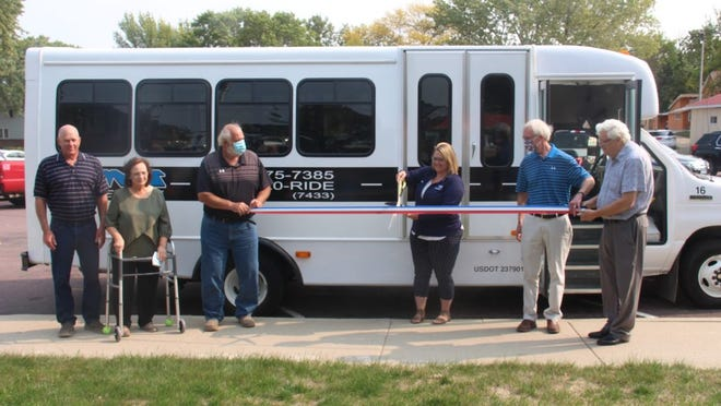 Allison Karau, surrounded by the Watonwan County Board and Joe McCabe, cuts the ribbon to officially welcome the new TMT bus into service.