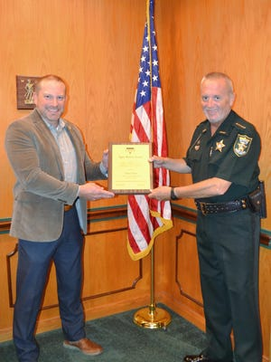 General Services Director Jason Sheffield presents the Bittner Award to Sheriff David Shoar.