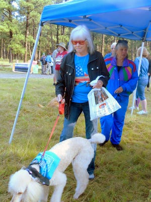 Marilyn Barnes and friend stopped to buy a momento of the annual Wandering Paws trek and headed for the starting line last year. The event this year is June 2.