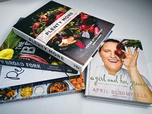 A stack of spring cookbooks, which are recommended for their attention to preparing meals with fresh produce.