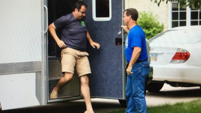 Jared Fogle, left, who rose to fame as the Subway pitchman, steps from a police evidence truck parked in the driveway of his Zionsville, Ind., home on Tuesday, July 7, 2015.