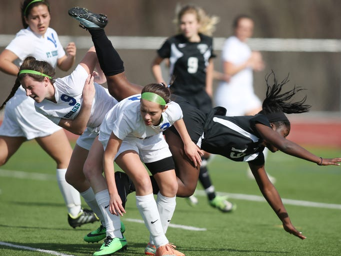Caravel's Katie Fullerton (right) is sent sprawling as St. Georges' Sara McVey (left) and Devin O'Reilly defend in the first half of Caravel's 3-1 win at St. Georges, Wednesday, April 9, 2014.