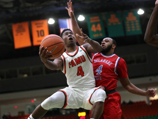 FAMU's Elijah Mayes lays the ball up past Delaware State's Johquin Wiley at the Al Lawson Center on Monday, Jan. 15, 2018.