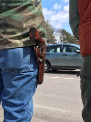 A holstered revolver hangs on the belt of a pro gun-rights activist at a rally on Shelburne Road in South Burlington on Saturday, April 7, 2018.