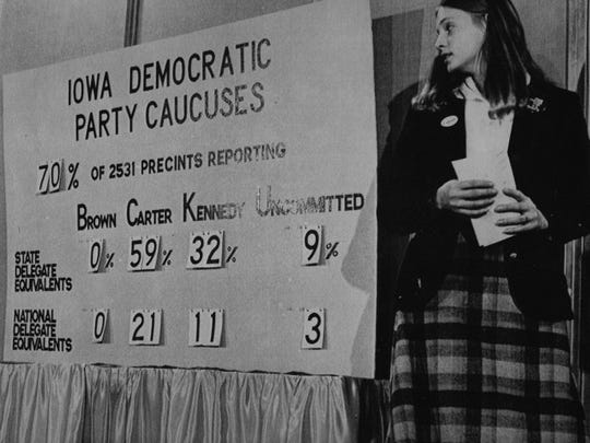 Sharon Bond, a worker at the Iowa Democratic Caucuses headquarters, pauses to check the latest precinct vote totals in the 1980 caucuses. New data from the Hawkeye Poll attempts to estimate how attached Iowans are to the traditional, physical caucus.