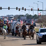 People ride horses and drive covered wagons down Government Street in Brandon Thursday morning on their way to the Dixie National Rodeo at the Mississippi Coliseum.