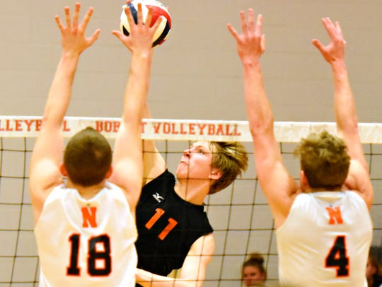 Central York's Braden Richard, center, slams the ball down while Northeastern's Nate Eyster, left, and Wyatt Hughes defend during boys' volleyball action at Northeastern High School last May. Richard will play his college volleyball at NCAA Division I St. Francis.
