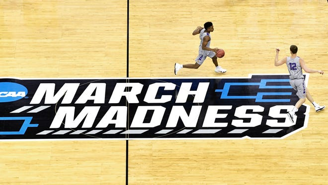 Lipscomb players Greg Jones (1) and forward Matt Rose (12) run past the March Madness logo as they practice to play North Carolina in the 2018 NCAA MenÕs Basketball TournamentThursday March 15, 2018, in Charlotte, NC