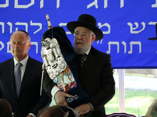Former Chief Rabbi of Israel, Rabbi Israel Lau, holding the Torah scroll flanked by Miles Berger, a trustee of the Rabbinical College of America, at the college's graduation on June 26, 2016 in Morris Township