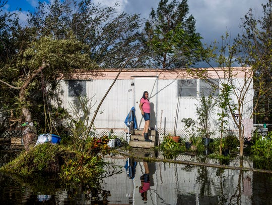 A woman walks in to her trailer from her flooded yard