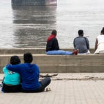 Friends gather on the wharf under the Second Street Bridge awaiting word on three missing members of a pontoon accident from Saturday night that left two dead. 7/6/15