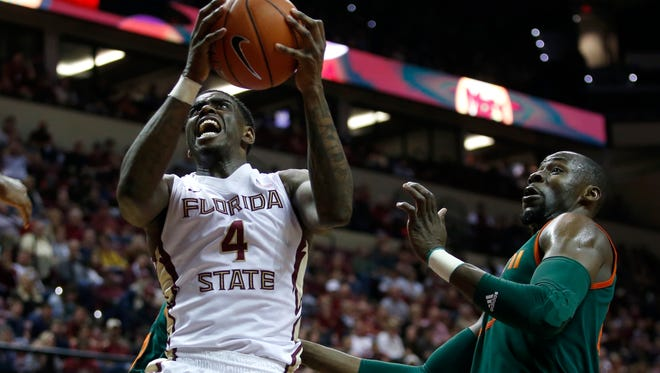 FSU's Dwayne Bacon charges past Miami's Tonye Jekiri for a layup during their game at the Tucker Civic Center last month.