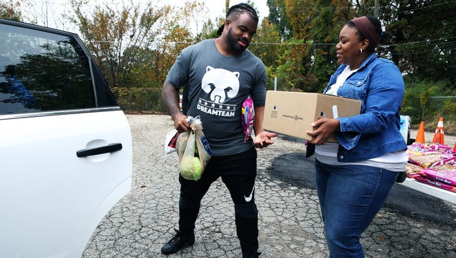 November 7, 2017 - Dontari Poe, a former University of Memphis football player and current defensive tackle for the Atlanta Falcons, is handed a food box from Tonie Reynolds, a member of the Order of the Eastern Star, Hannah Number 20 of Southaven, MS, as they distribute groceries to 200 needy families at The Healing Center, at 3885 Tchulahoma Road, on Tuesday. The event was possible through Poe's foundation, Poeman's Dream Foundation, and the Memphis Food Bank.