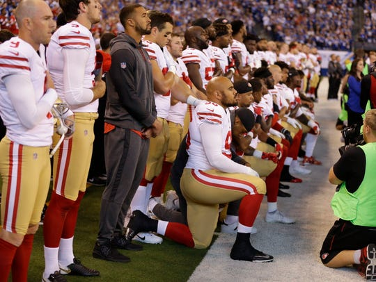 Members of the San Francisco 49ers kneel during the