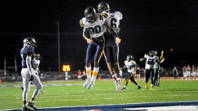 Deon Senegal and Eric Tolivour celebrate after a touchdown as the St Thomas More Cougars take on the Carencro Bears. October 14, 2016.