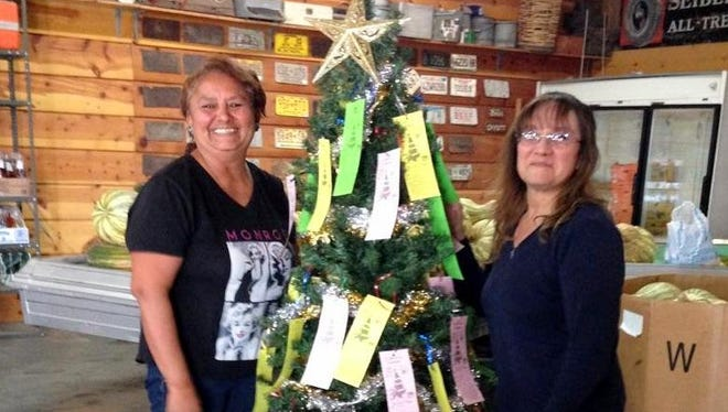 Esperanza Lozoya, left, and an unidentified volunteer set up a Tree of Hope at Diaz Farms Produce Store at 2485 Silver City Hwy. NW.