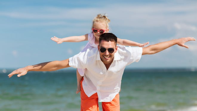 family, travel, vacation, adoption and people concept - happy father with little girl in sunglasses having fun on summer beach