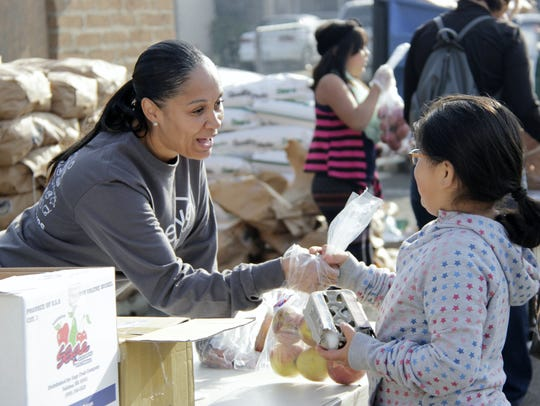 Fawn Perryman, of Jostens, hands out apples at the annual Visalia Emergency Aid Council Thanksgiving dinner pick-up.