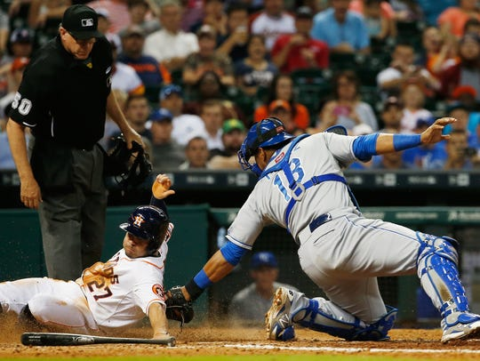 Houston Astro Jose Altuve slides into home plate under
