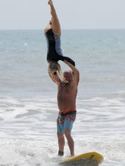 Bear Woznick lifts Cindy Davis during the Easter Surfing Festival at Lori Wilson Park.