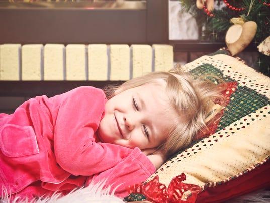 Little cute girl sleeping under x-mas Tree waiting Santa Claus