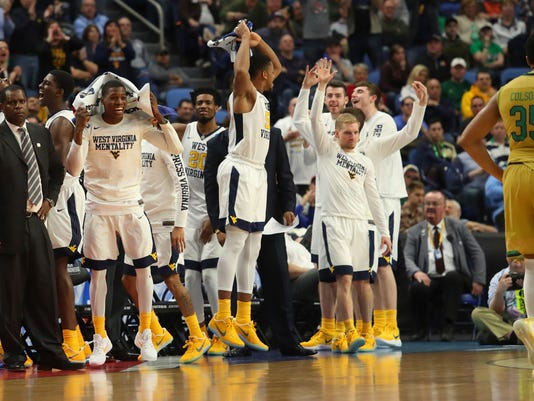 West Virginia players celebrate in the closing moments of their 83-71 win against Notre Dame in a second-round men's college basketball game in the NCAA Tournament, Saturday, March 18, 2017, in Buffalo, N.Y. (AP Photo/Bill Wippert)