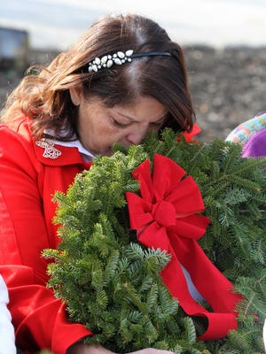 Anna Ortiz of Somerdale, an American Gold Star Mother and mother of Army Sergeant Hector L. Ortiz, who committed suicide in 2012, hugs a wreath she received from Meghan Murray, 13, a Civil Air Patrol cadet from Orono, Maine, during the Wreath Laying Ceremony presented by Wreaths Across America at the New Jersey Vietnam Veterans' Memorial in Holmdel, NJ Wednesday December 9, 2015.