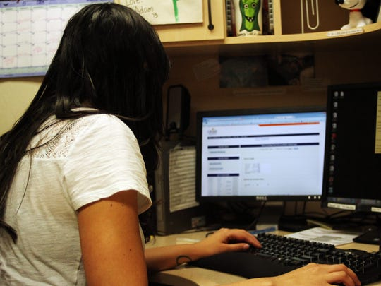 Left, Kayla Ortiz, program assistant and former volunteer at the Crisis Call Center in Reno, works at her desk on June 20. The center, which also receives phone calls, is the first in the nation to offer help via text messages.