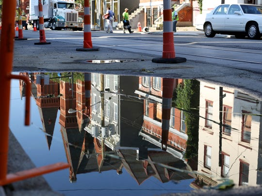 Some of the rehabbed buildings along Elm Street are reflected in this puddle.