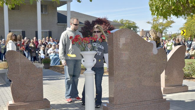 Dan and Kathryn Plamondon add a flower to the memorial in honor of their infant daughter.