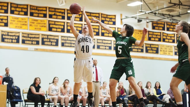 Essex's Olivia Duncan (40) leaps past St. Johnsbury's Sadie Stetson (5) during a high school girls basketball earlier this season.