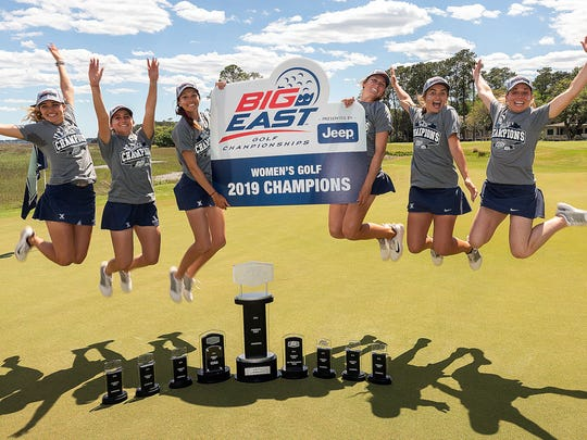 The Xavier women's golf team celebrates winning the
