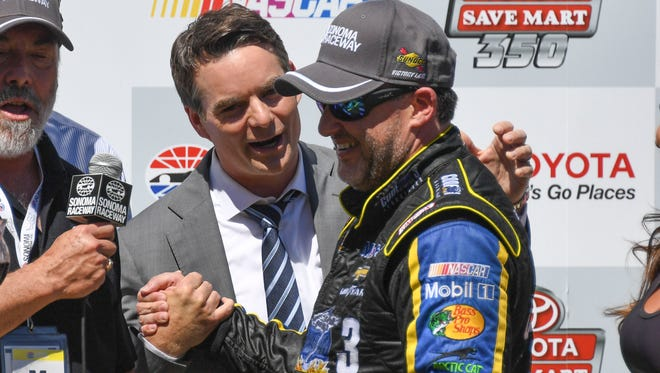 Sprint Cup Series driver Tony Stewart (14, right) is congratulated by former driver Jeff Gordon (left) in victory lane during the Toyota Save Mart 350 at Sonoma Raceway.