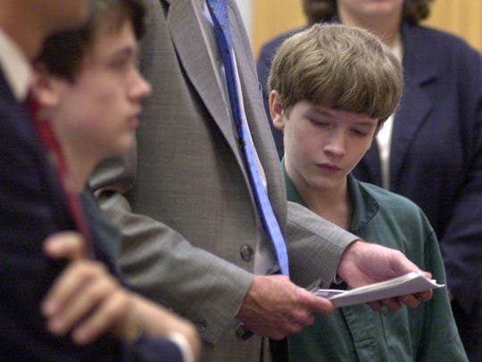 --11-15-02, 6aGary McCracken@PensacolaNewsJournal.com--Alex King, 13, reads notes held by his attorney, James Stokes, during announcement of the mediation outcome in the King brothers' murder case. Derek King,14, is at left.